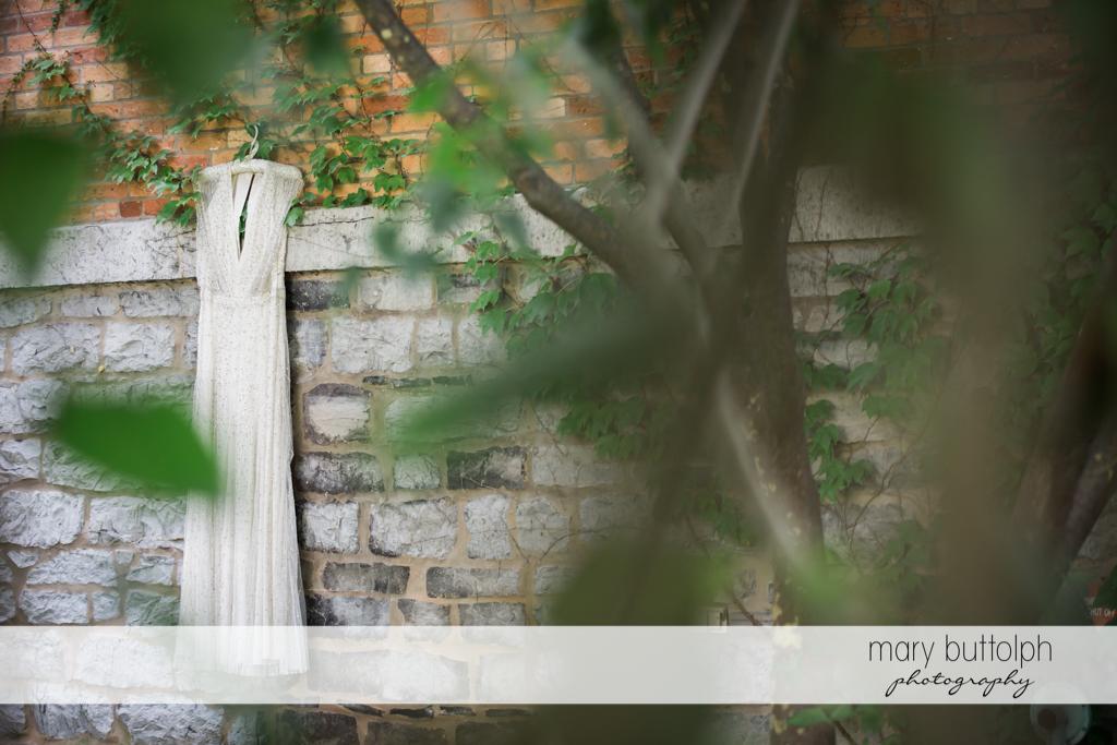 Bride's wedding dress hangs on a brick wall in the garden at Aurora Inn Wedding