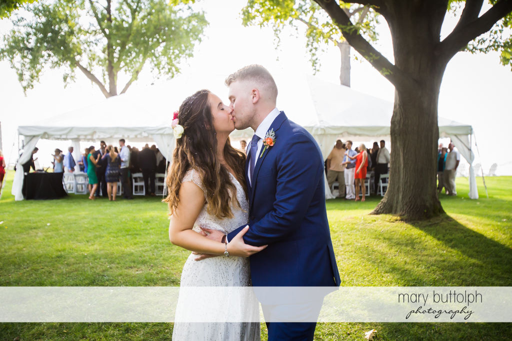 Couple kiss in front of guests at Aurora Inn Wedding