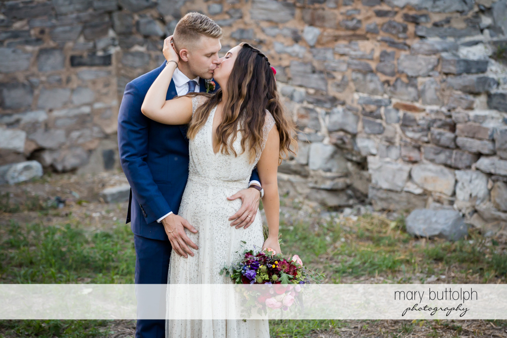 Couple kiss in front of a brick wall at Aurora Inn Wedding