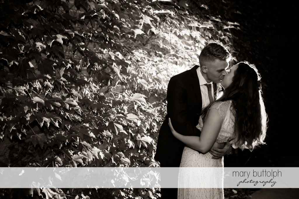 Couple kiss in front of plants at Aurora Inn Wedding
