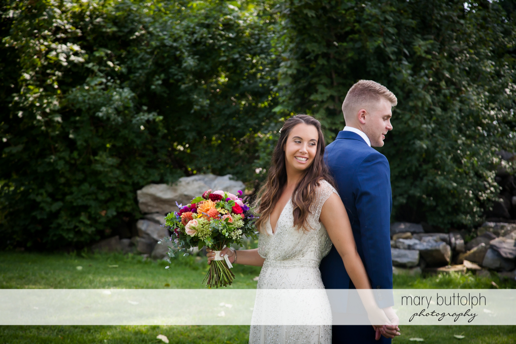 Couple with flowers pose in the garden at Aurora Inn Wedding