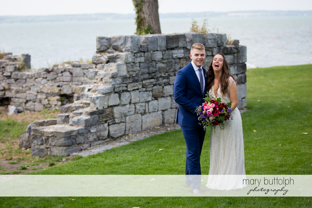 Couple pose in front of a brick wall near the lake at Aurora Inn Wedding