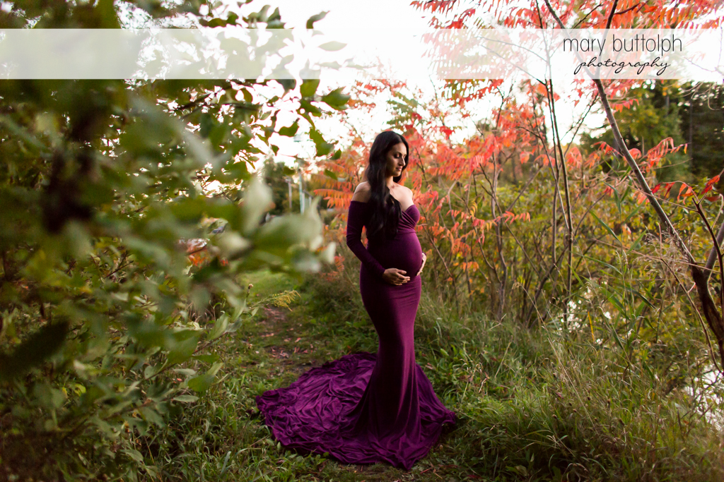 Woman in gown with baby bump in the garden at Skaneateles Maternity Photography