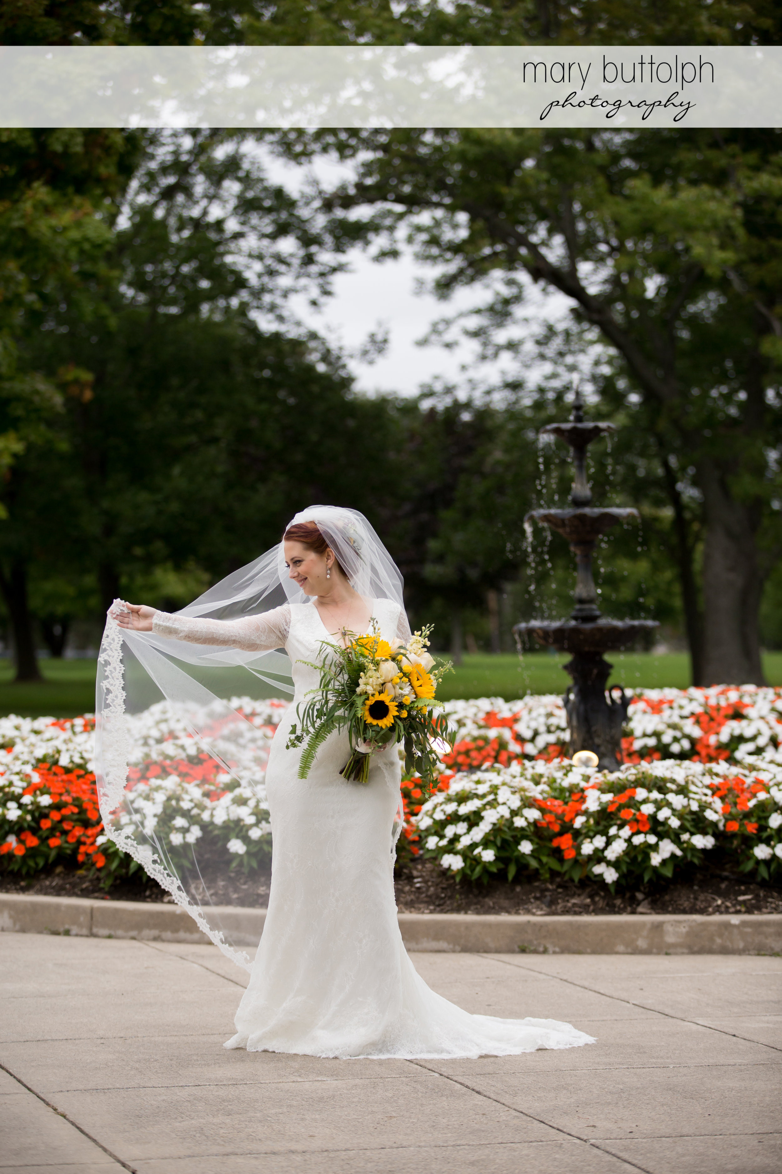 Bride shows off her wedding dress in the garden at Emerson Park Pavilion Wedding