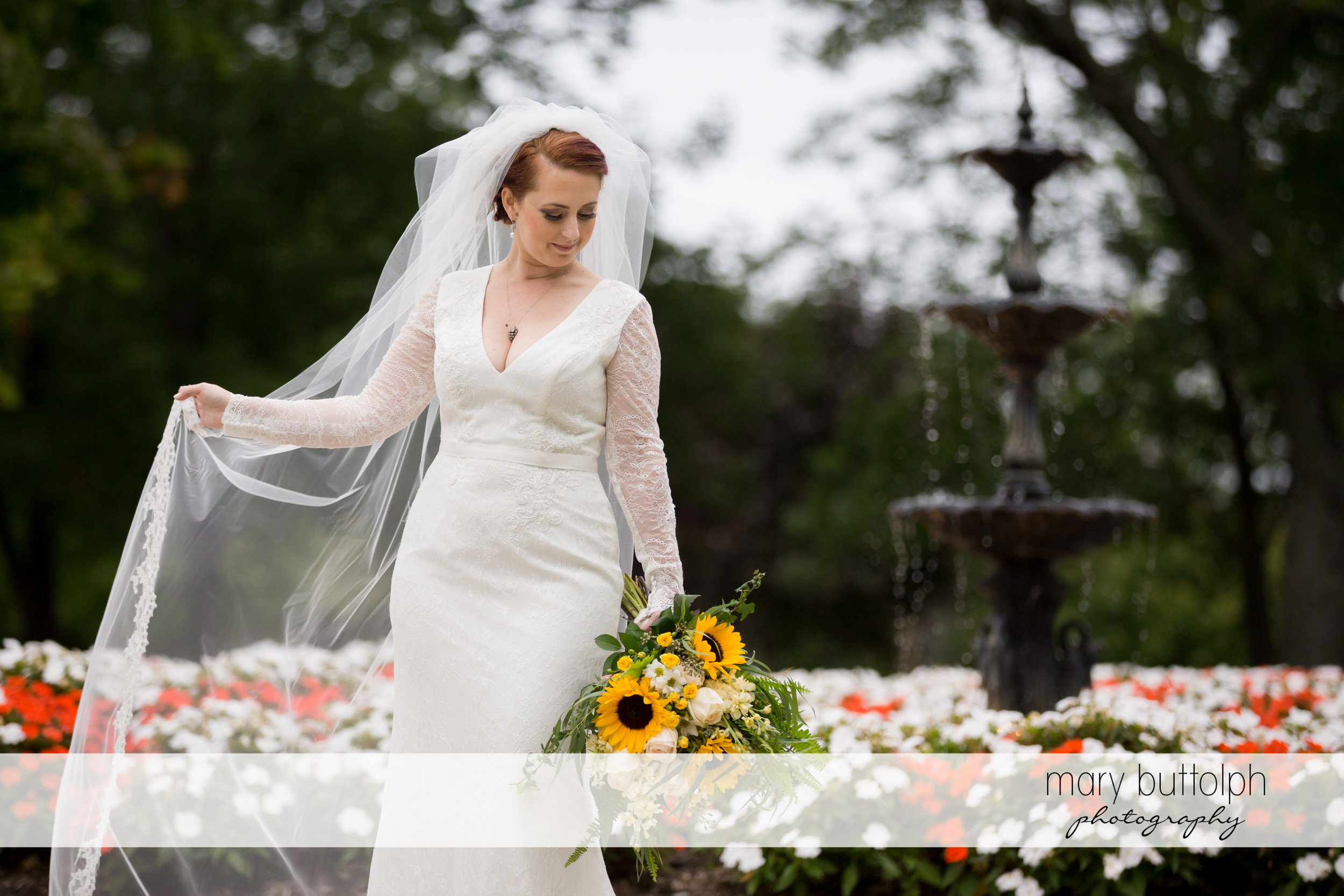 Bride strikes a pose while holding sunflowers in the garden at Emerson Park Pavilion Wedding