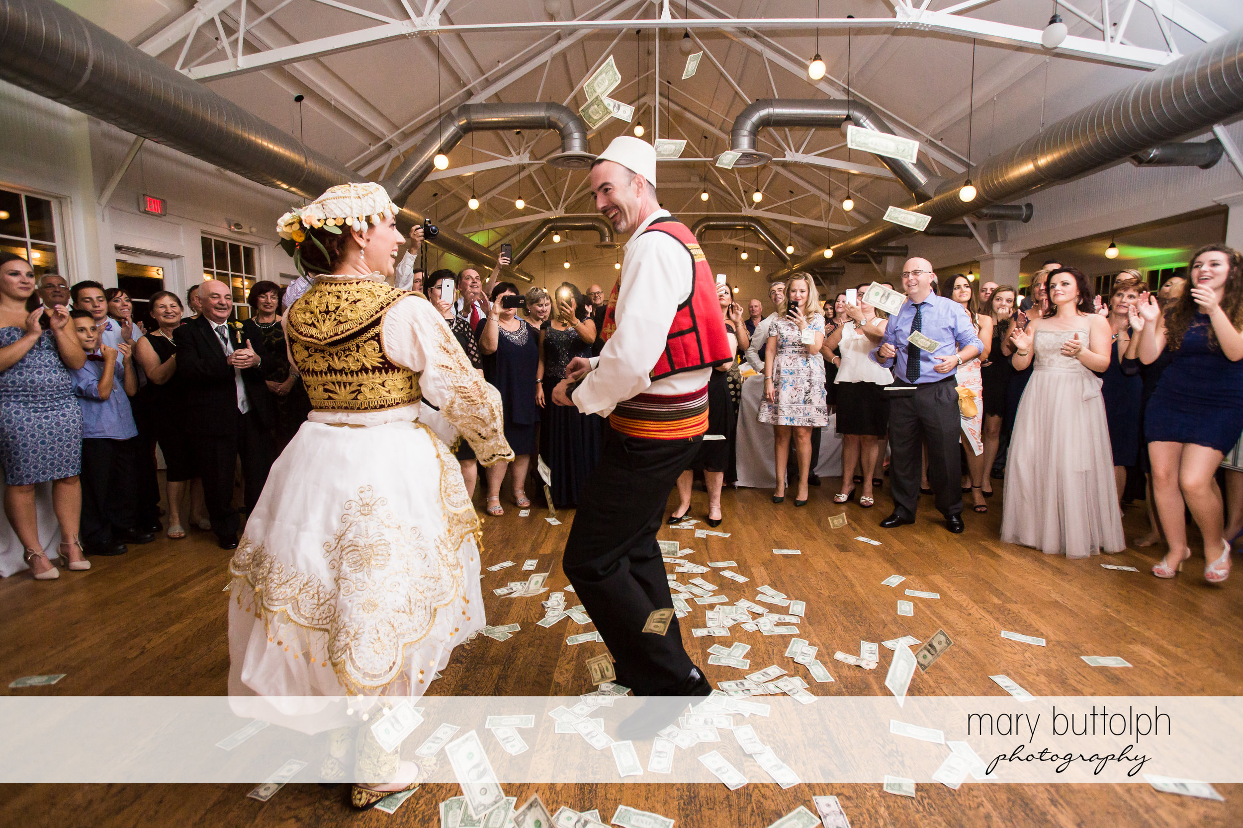 Couple wearing traditional Albanian costumes dance on money scattered on the floor at Emerson Park Pavilion Wedding