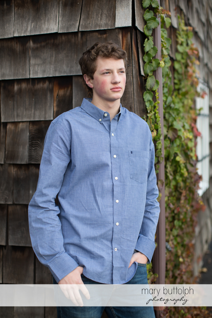 Teen in a serious mood beside a wooden structure at Skaneateles Senior Photography