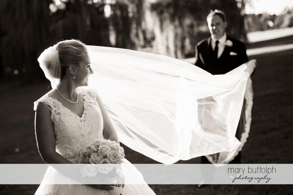 Groom holds bride's wedding veil at SKY Armory Wedding