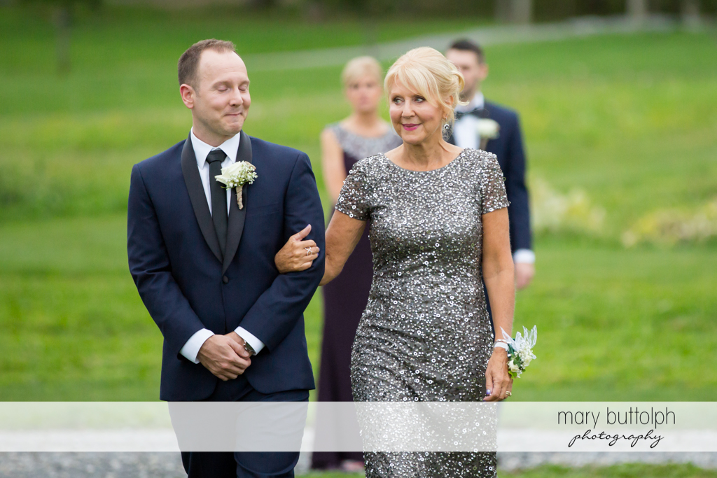 Groom is escorted by his mother in the garden at Anyela's Vineyards Wedding