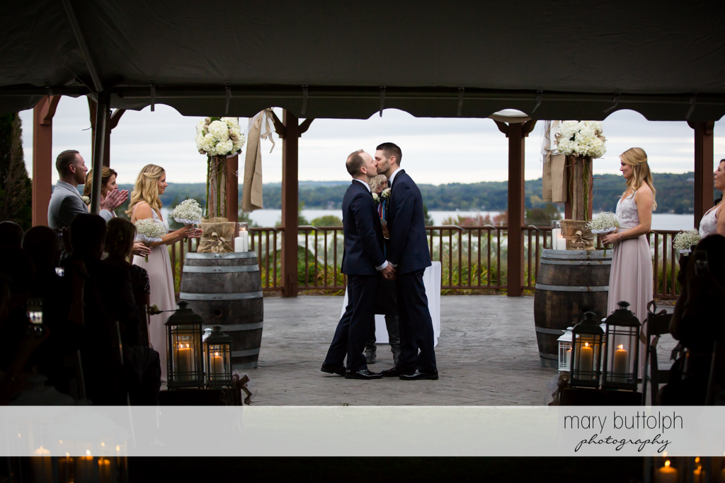 Same sex couple kiss after the wedding as guests look on at Anyela's Vineyards Wedding