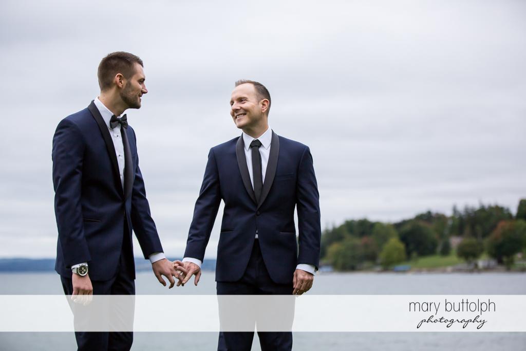 Couple holding hands by the Skaneateles Lake before Anyela's Vineyard Wedding