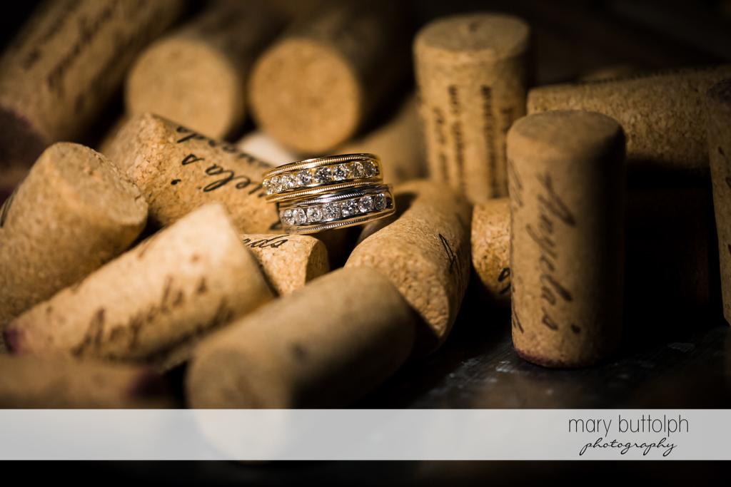 Same sex couple's wedding rings on top of corks at Anyela's Vineyards Wedding