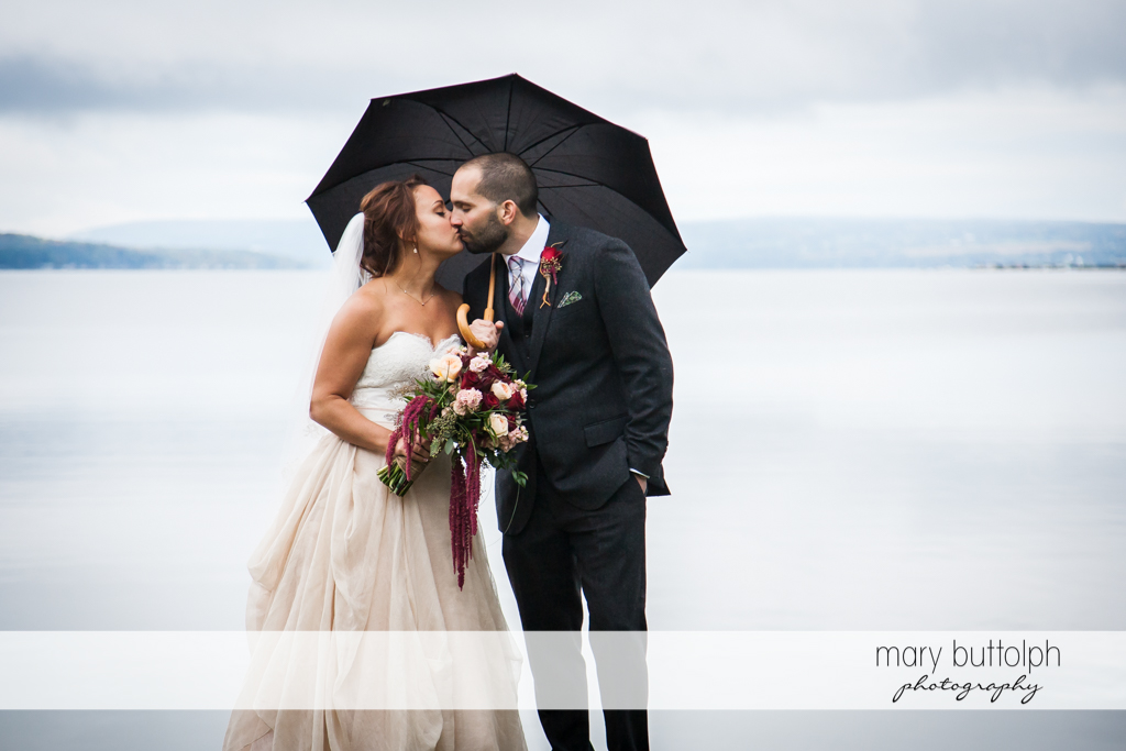 Bride and groom kissing under an umbrella at Sherwood Inn WEdding