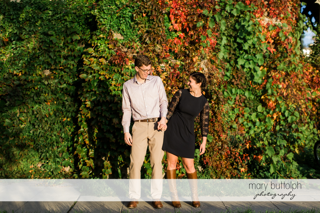 Couple hold hands in garden at Cornell University Engagement