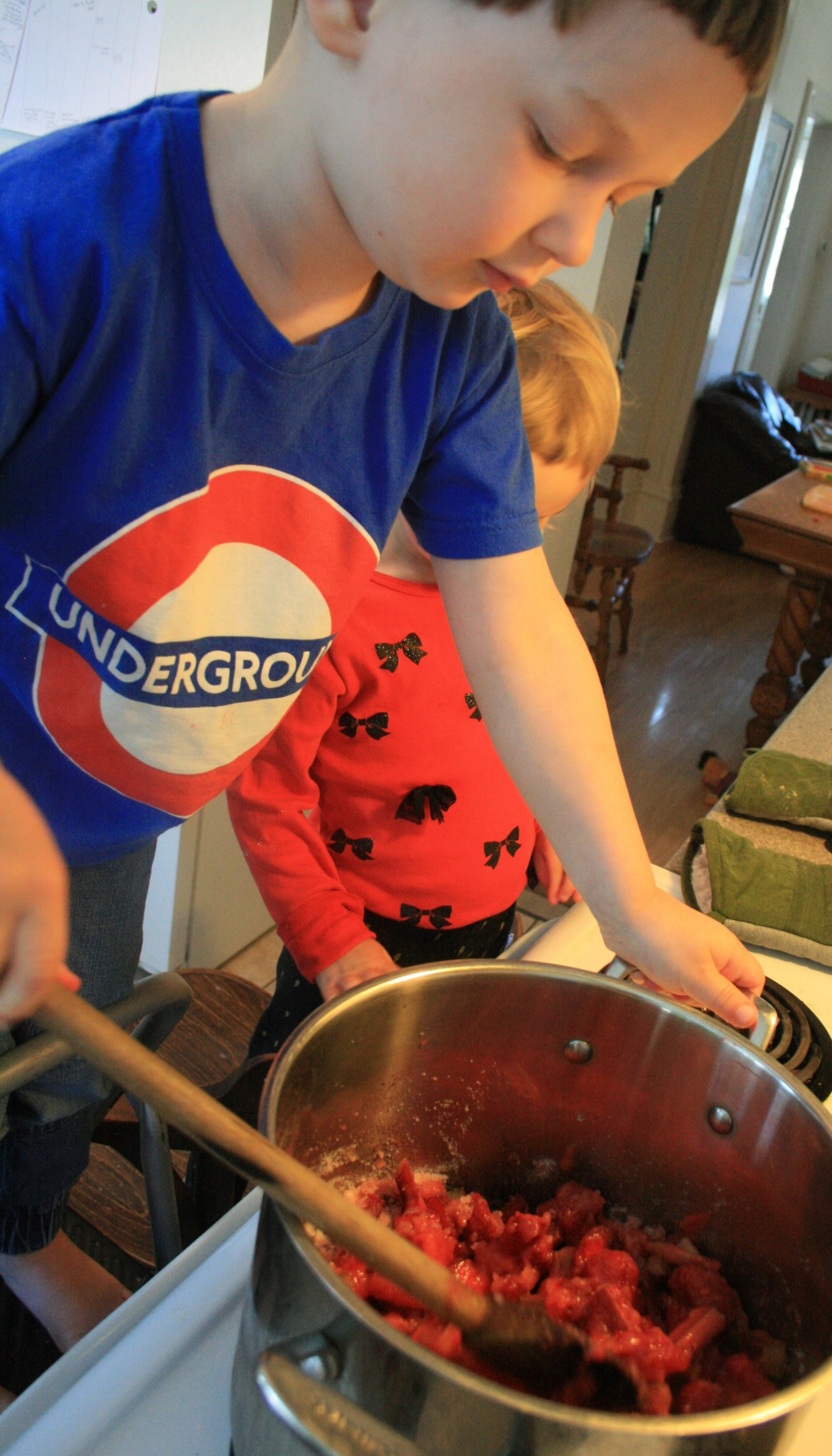 On a stool stirring the ingredients together. Sturdy stool, deep pot, long spoon, watchful parental eye.