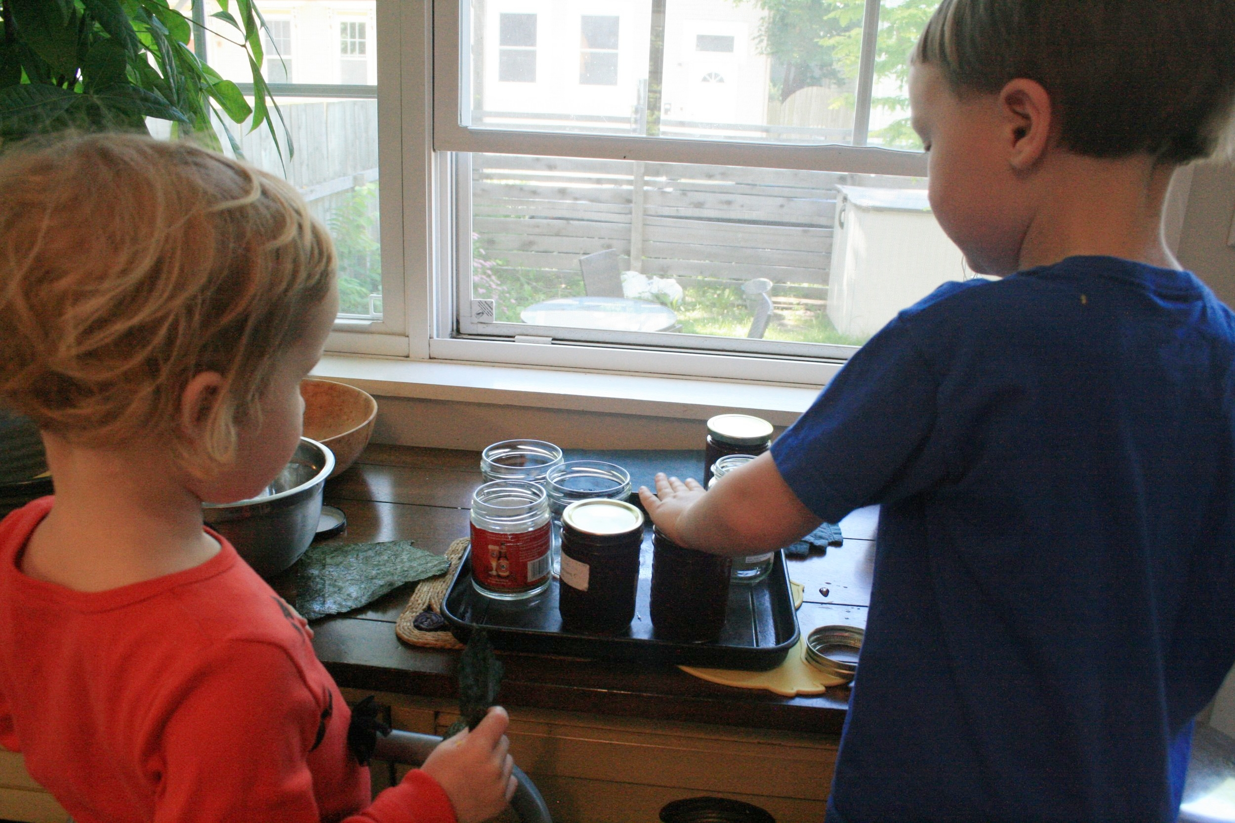 Pressing the lids down. Take care - the jam, and the jars, are hot!