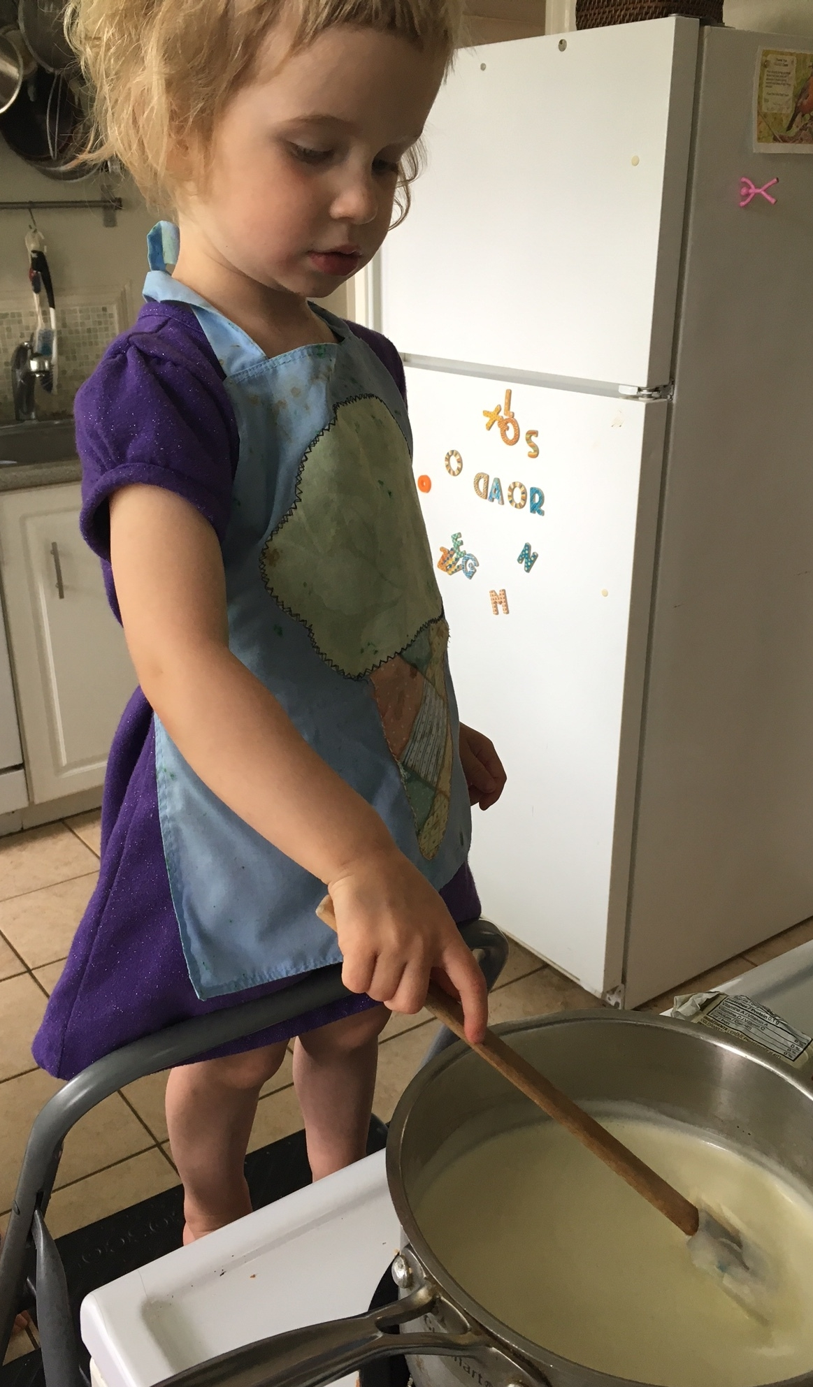 Polly (3) stirring the custard for the ice cream, as it thickens on the stove. She even chose a thematic apron for the occasion