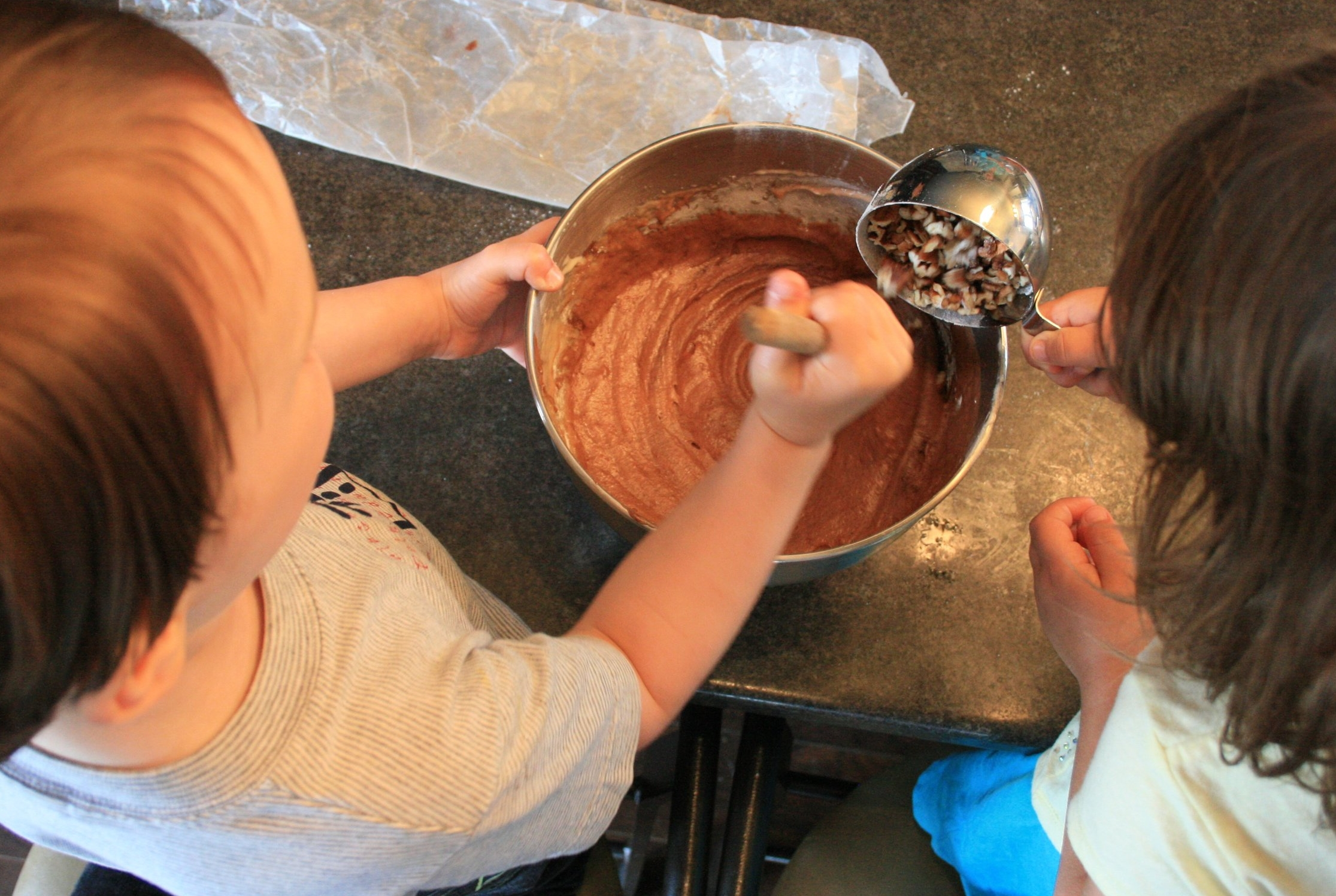 Five-year-old cousins working together: adding pecans to the brownie batter.