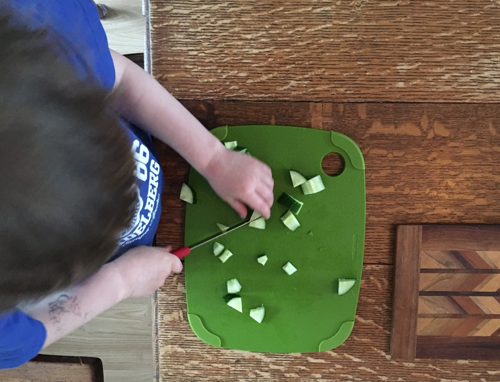 Cash at age 4, using a small, serrated knife to chop cucumbers