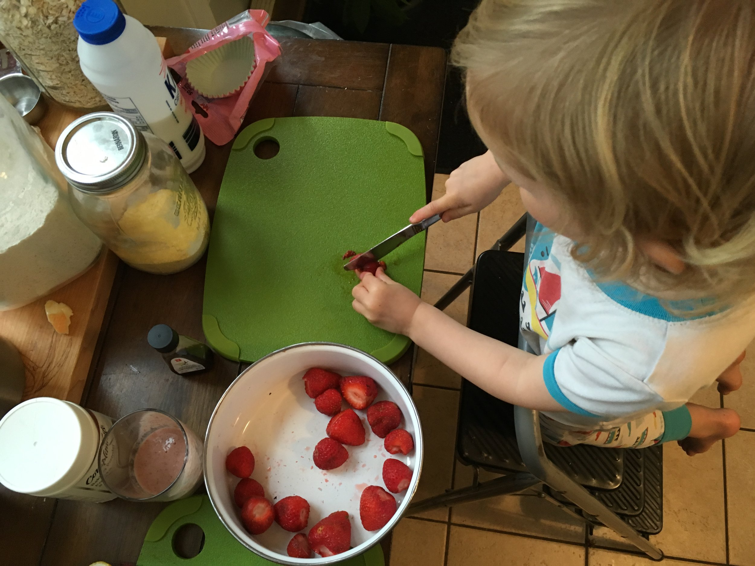 Three-year-old knife skills. Butter knife, that is. Note her snacks for the lesson, on the left: smoothie and piece of stinky cheese!