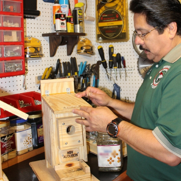Adolph Jaurez adds the finishing touches to a bluebird nest box.