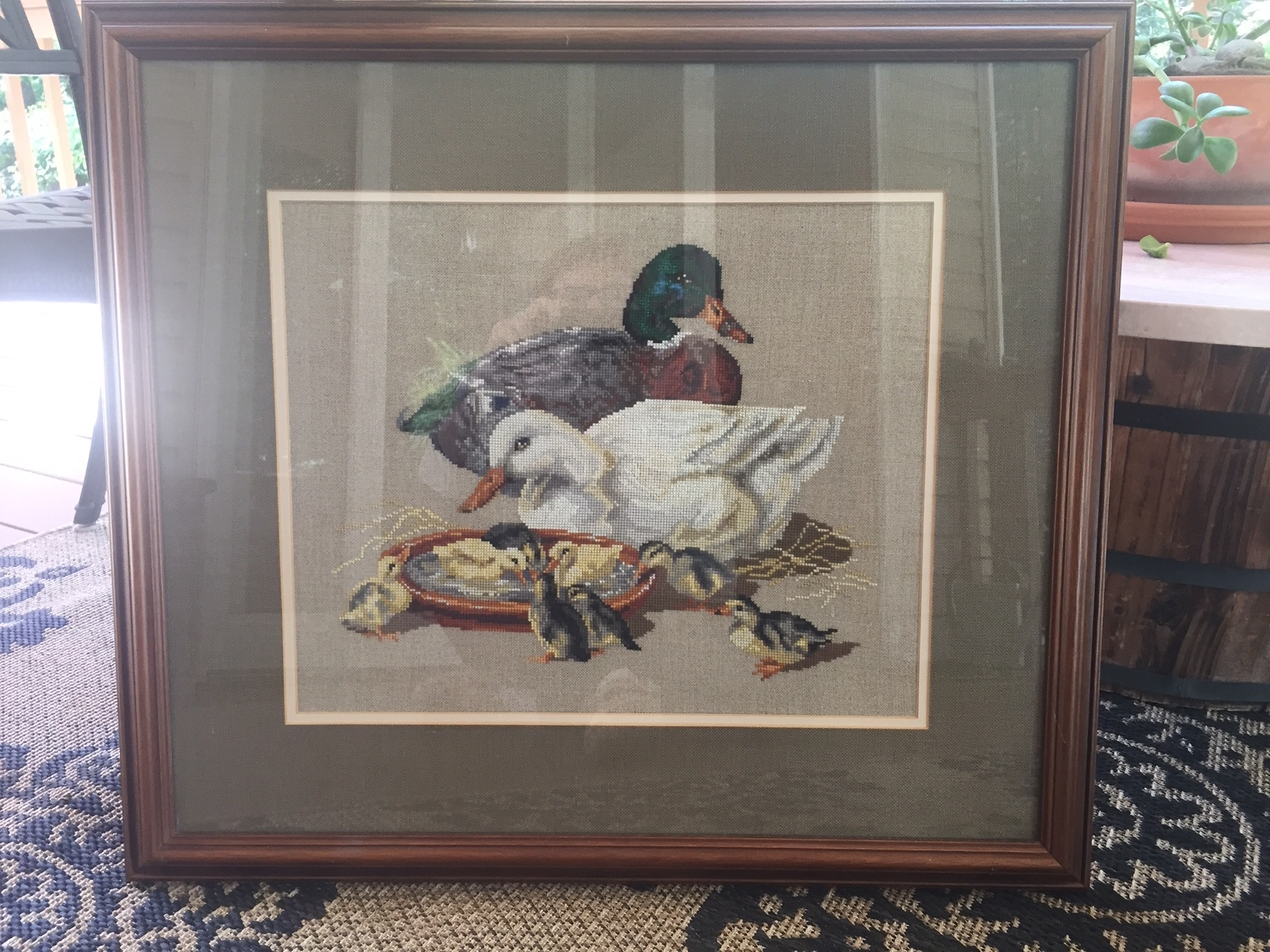Professionally framed needlepoint of duck family donated by Pattie Swenson