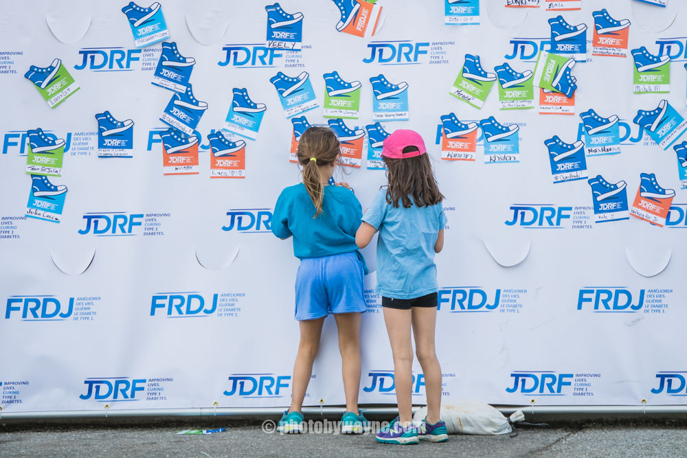 66-two-young-girls-looking-at-sponsor-wall.jpg