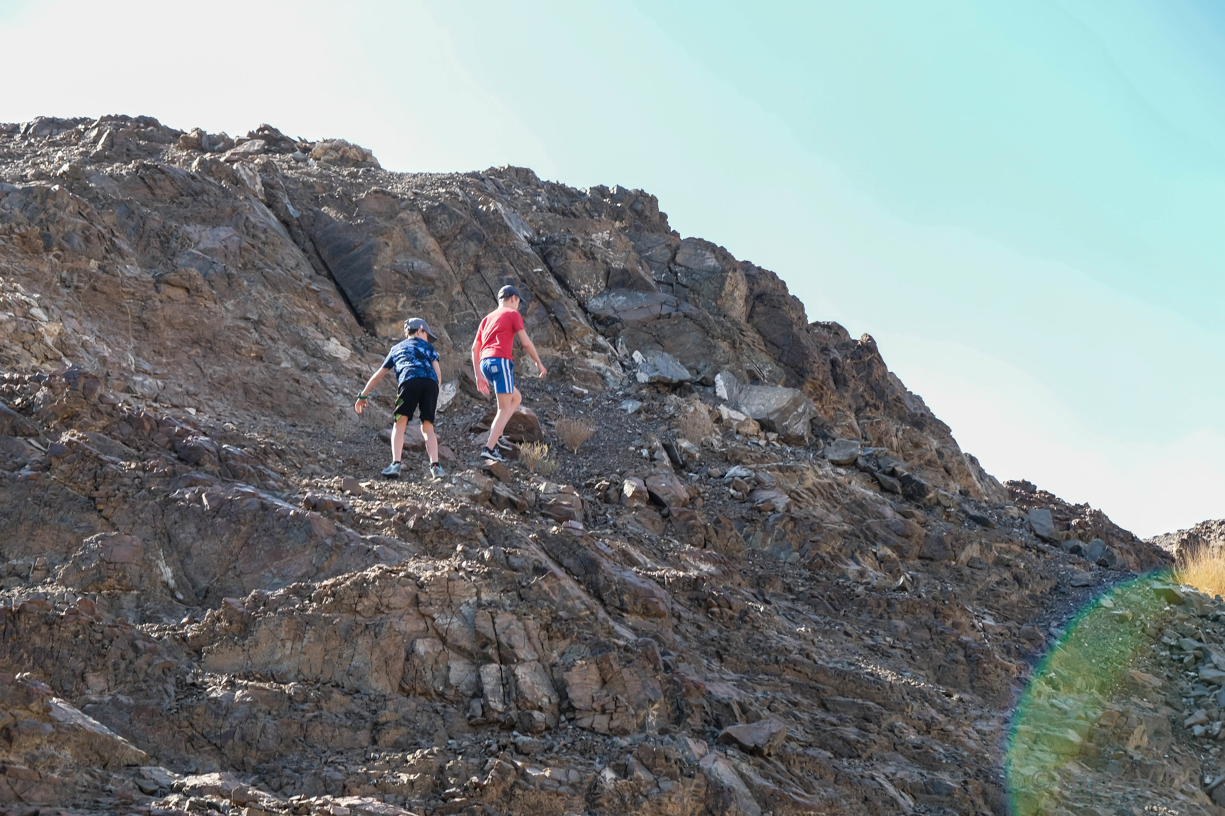 boys climbing rocks on camel farm hike UAE12.jpg