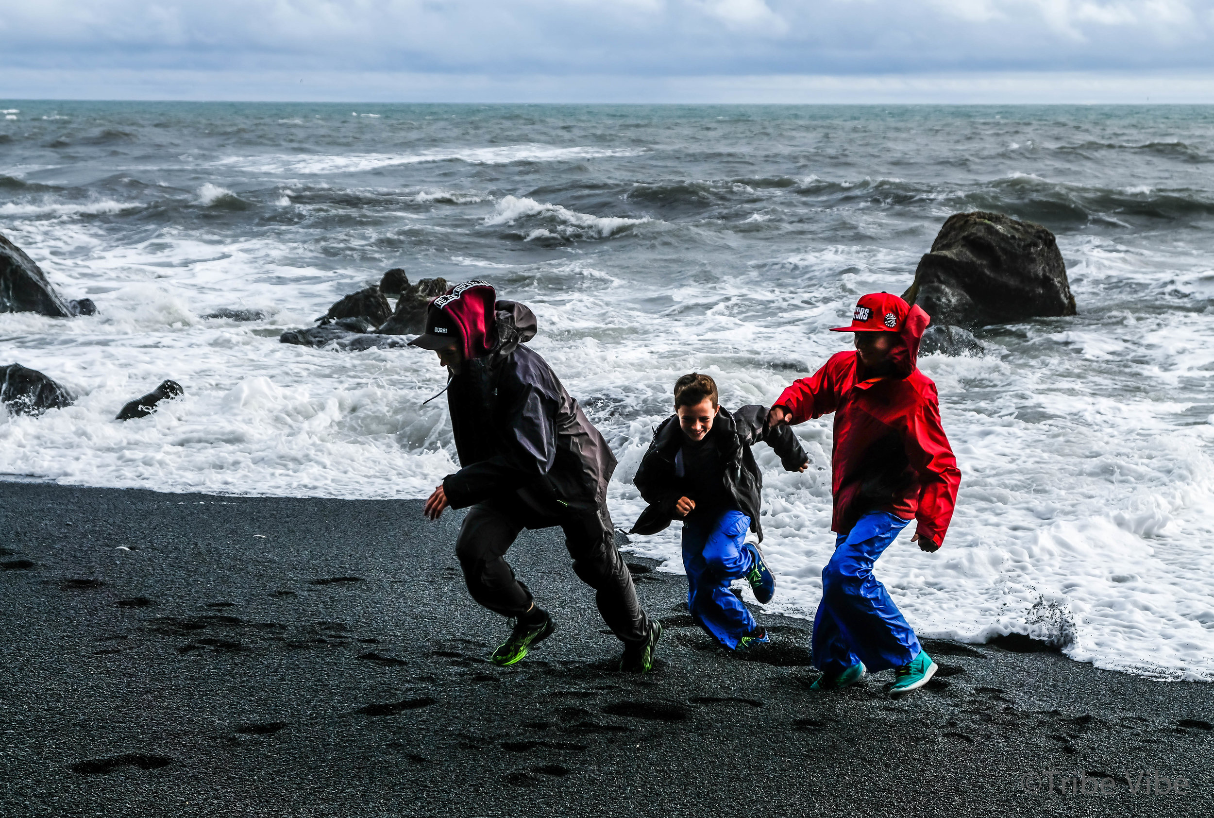 Chasing waves by the shore in Reynisdrangar, Iceland. Family road trip through Iceland.