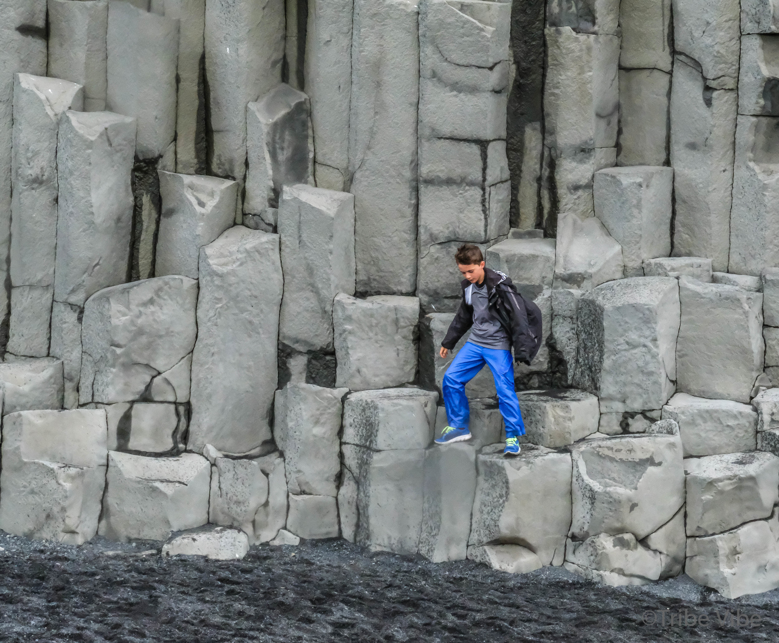 climbing the basalt rocks in Reynisdrangar, Iceland. Family trip to Iceland.