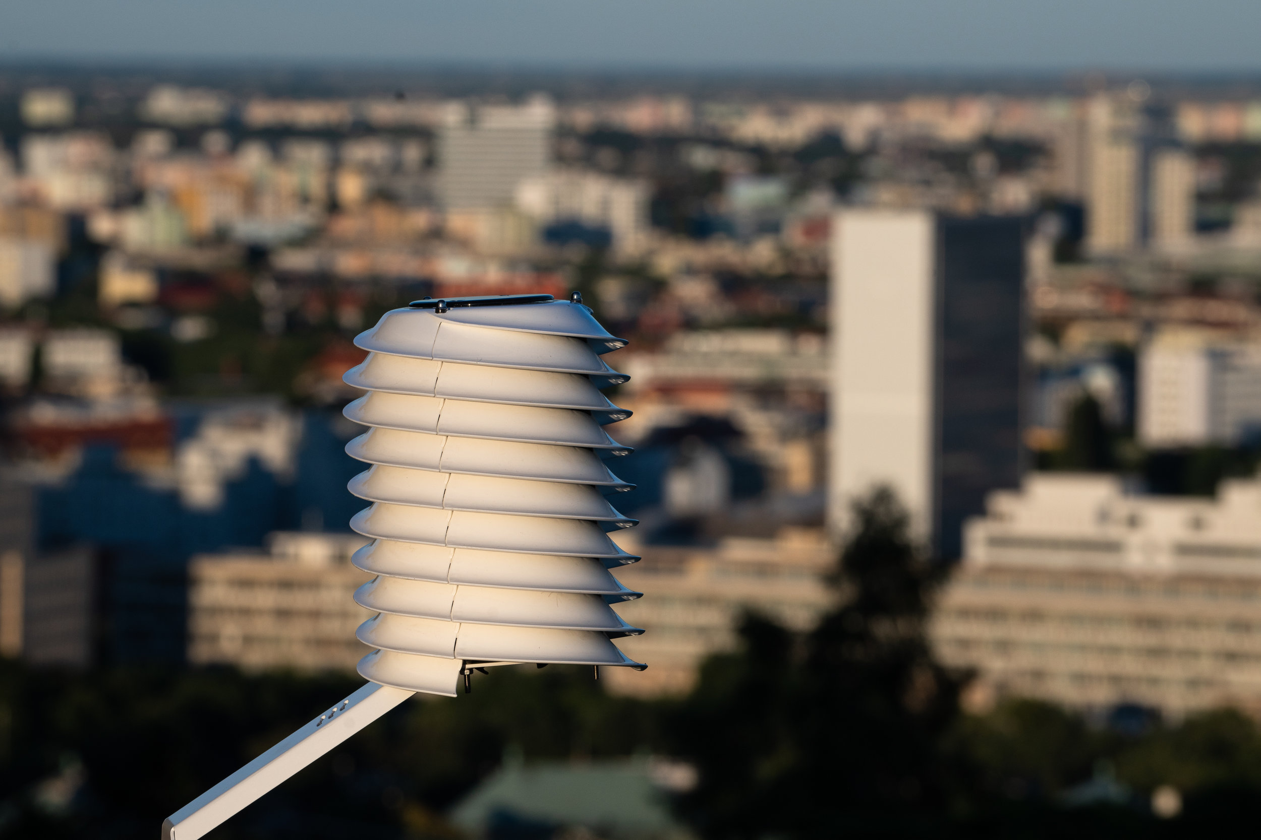 smart-cities weather station overlooking a city skyline in sunset