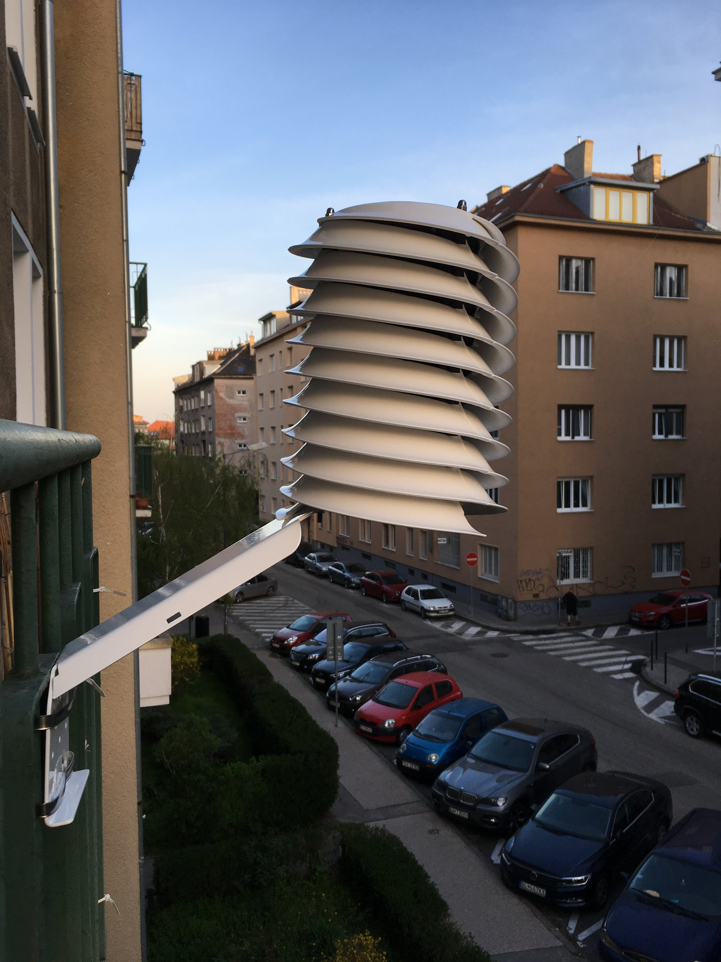 apartment building balcony weather station overlooking a city street