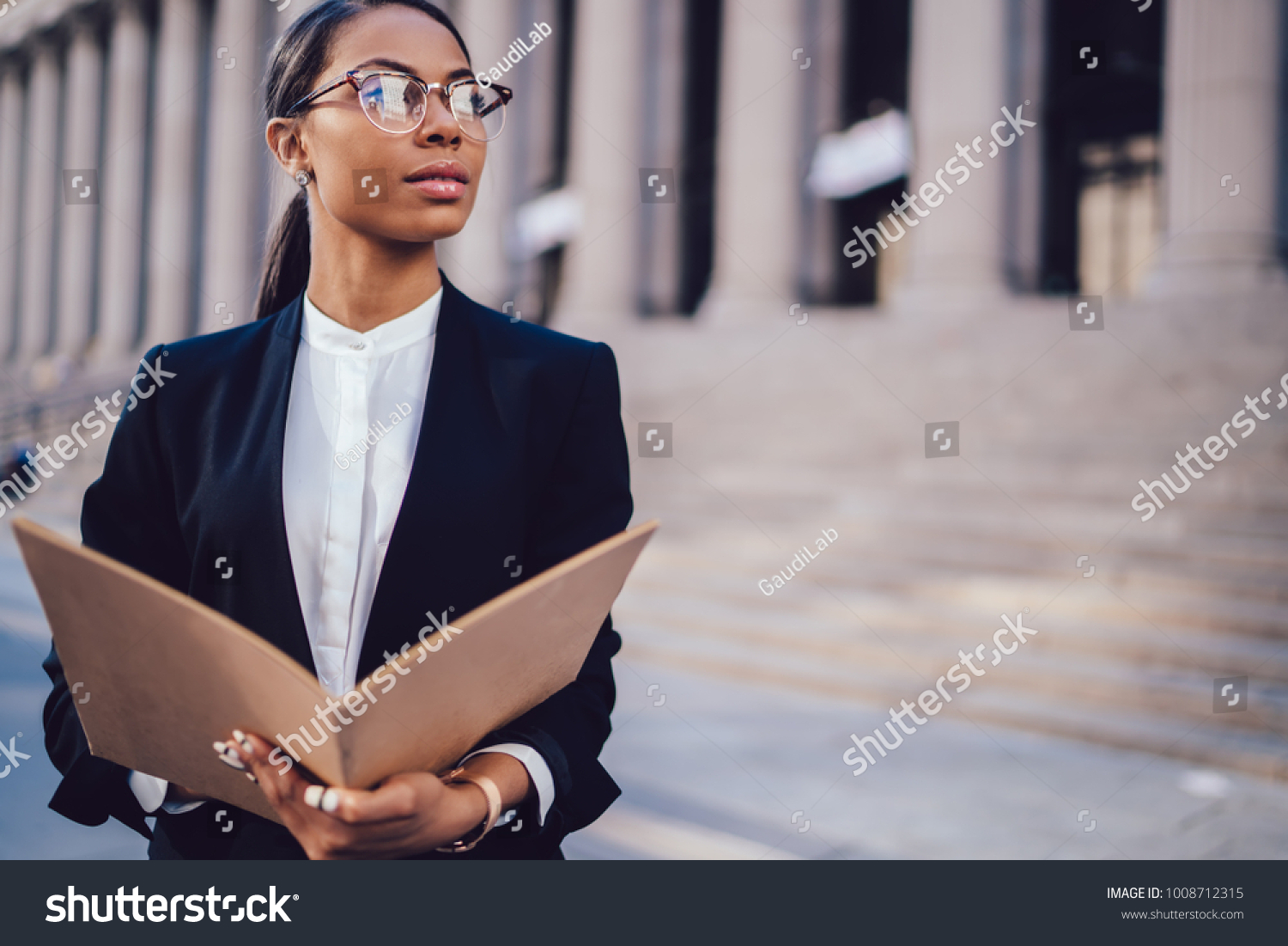 stock-photo-thoughtful-dark-skinned-female-financial-manager-in-black-suit-holding-folder-in-hands-while-1008712315.jpg