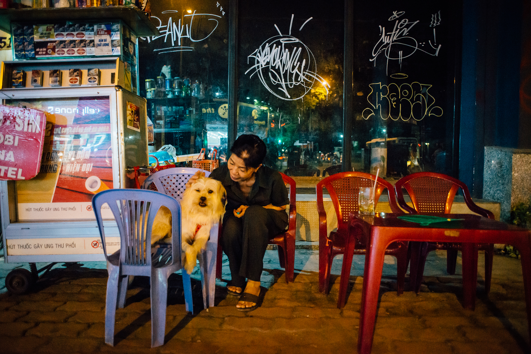 A woman and her dog enjoy an iced green tea on the streets of Ho Chi Minh City.
