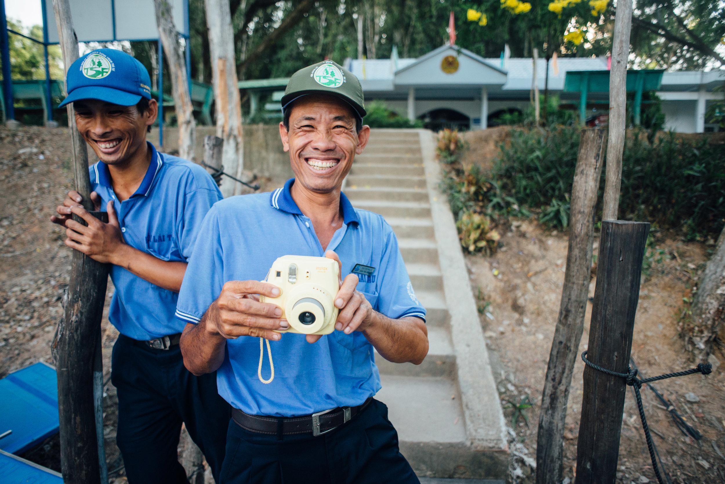 Two men play with a Polaroid camera in the An Giang Provence of Vietnam.