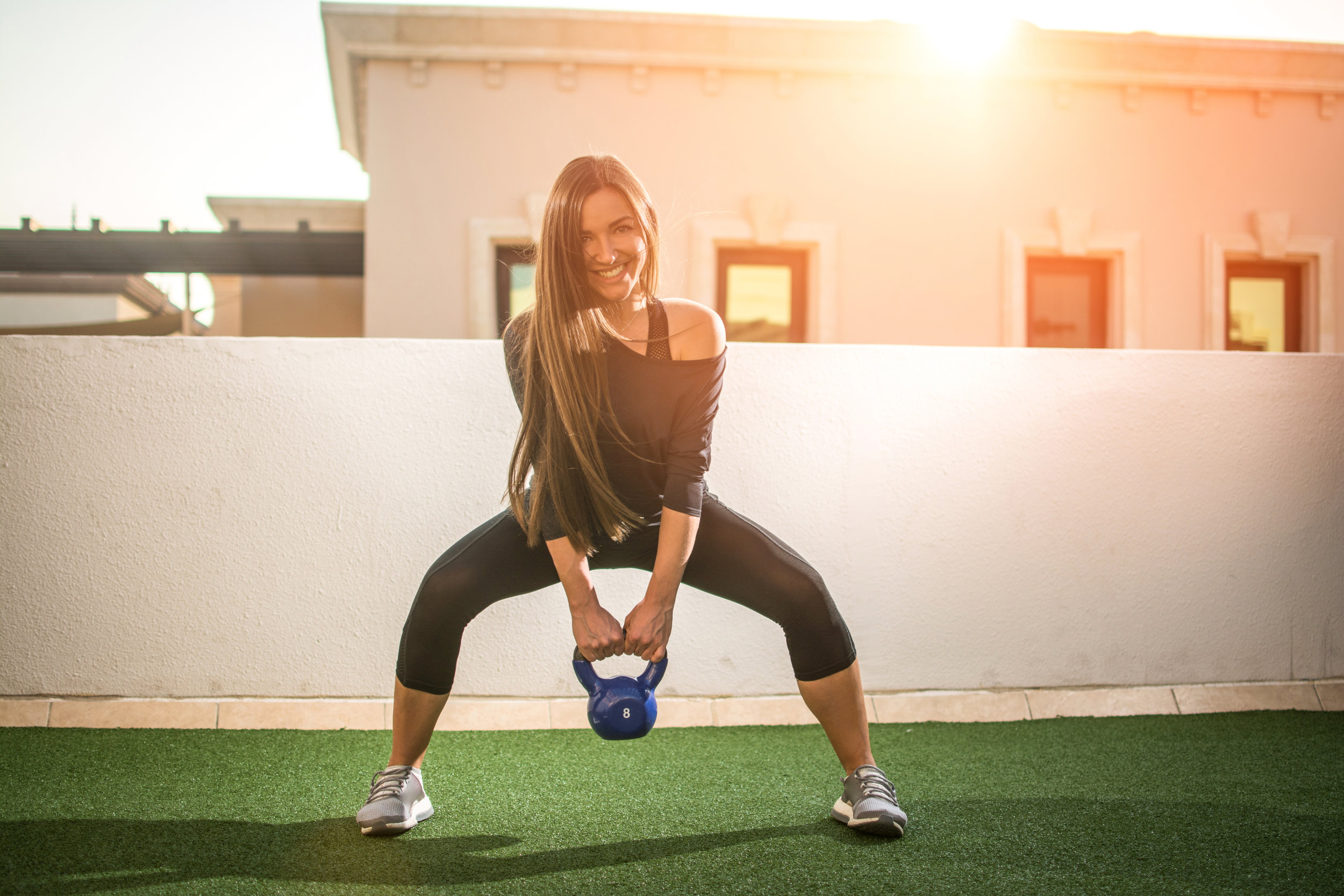 Sporty woman in squat position exercising with kettlebell outdoors during sunset.