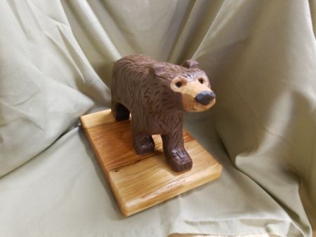 Hand carved brown bear - smiley face front view.