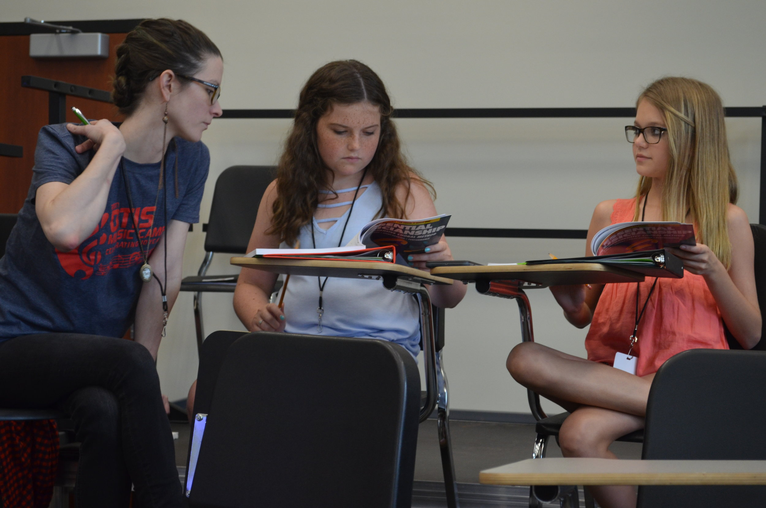 Coach Chelsea helping campers through music theory exercises.