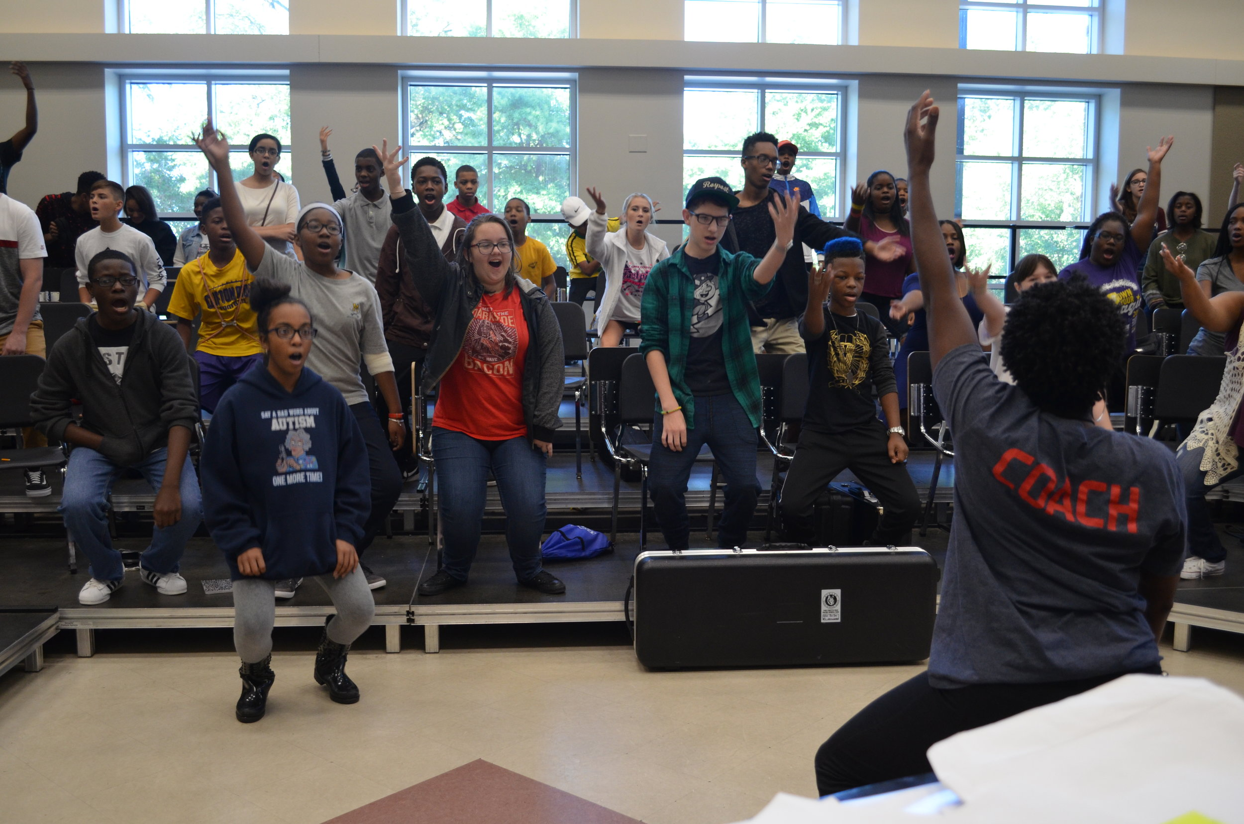 Coach Jayme taking campers through vocal warm ups.