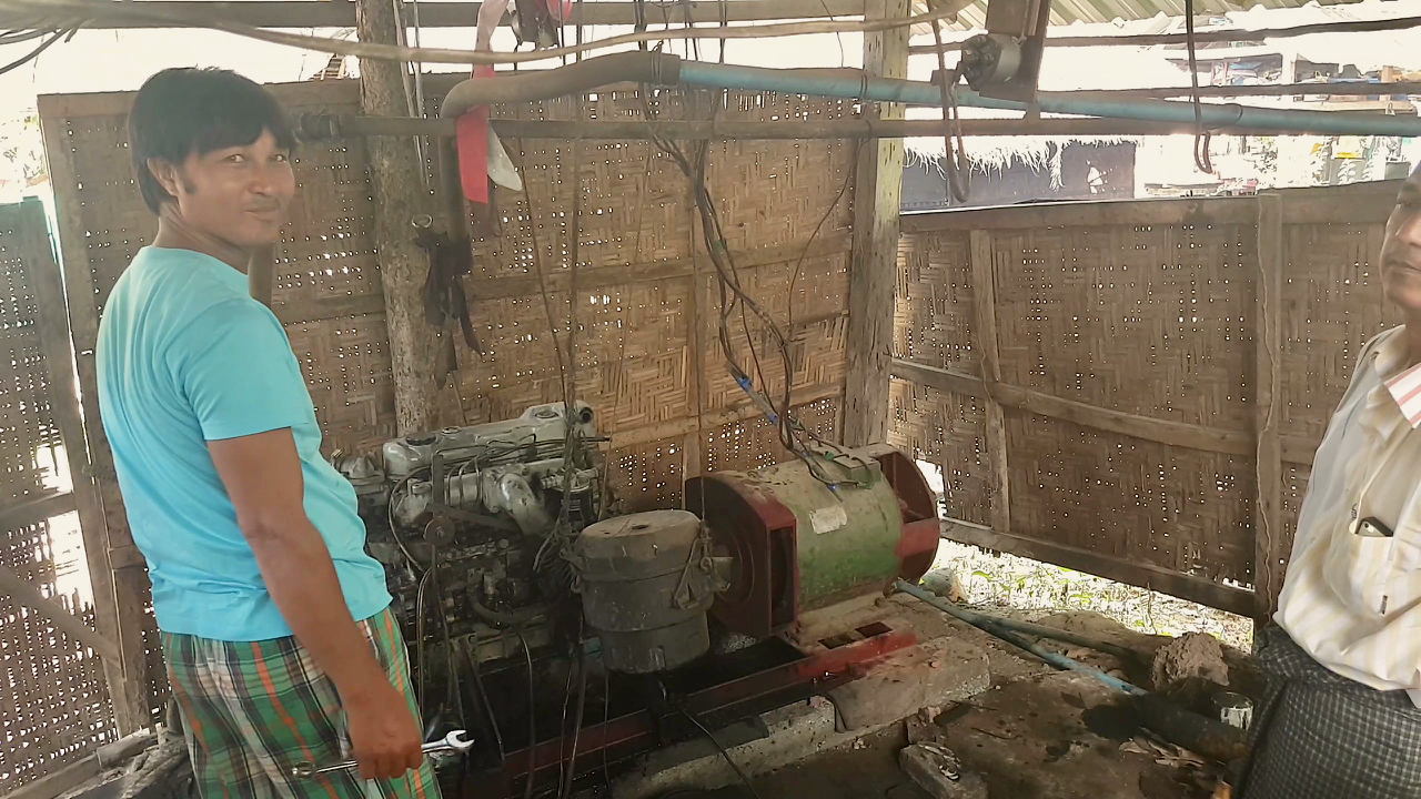 Aung Moe Win proudly showing off his generator as he gives us a tour of the mini-grid. Every night at 6 PM, he turns it on with the crank of a wrench, providing basic but necessary lighting and charging to his community.