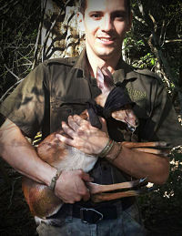 Our ecologist, Axel Hunnicutt, holding a suni (Neotragus moschatus) during research in 2016.