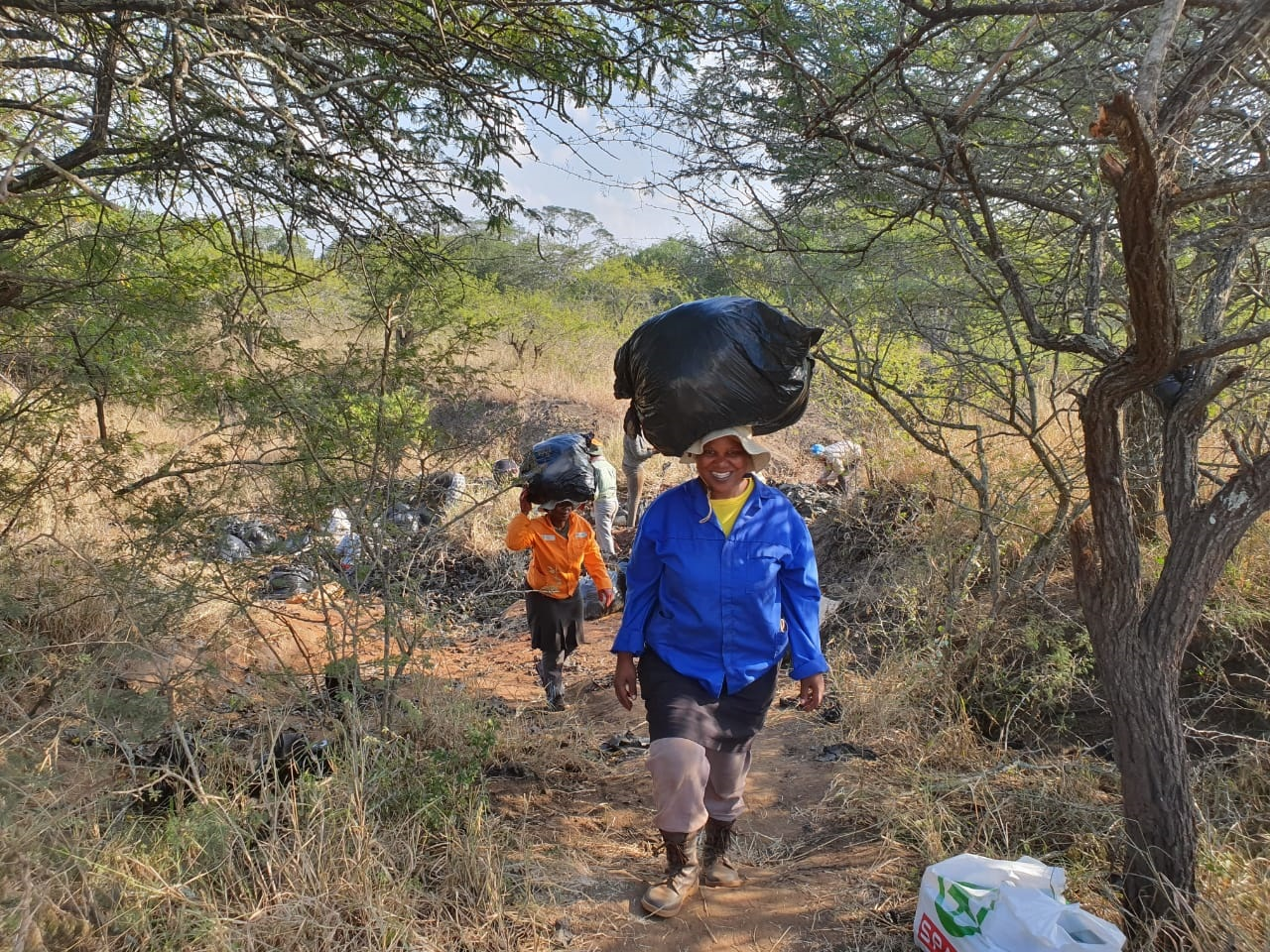 Green Mambas removing plastic, leftover from a negligent pineapple farmer, on Wild Tomorrow Fund's Ukuwela Conservancy.