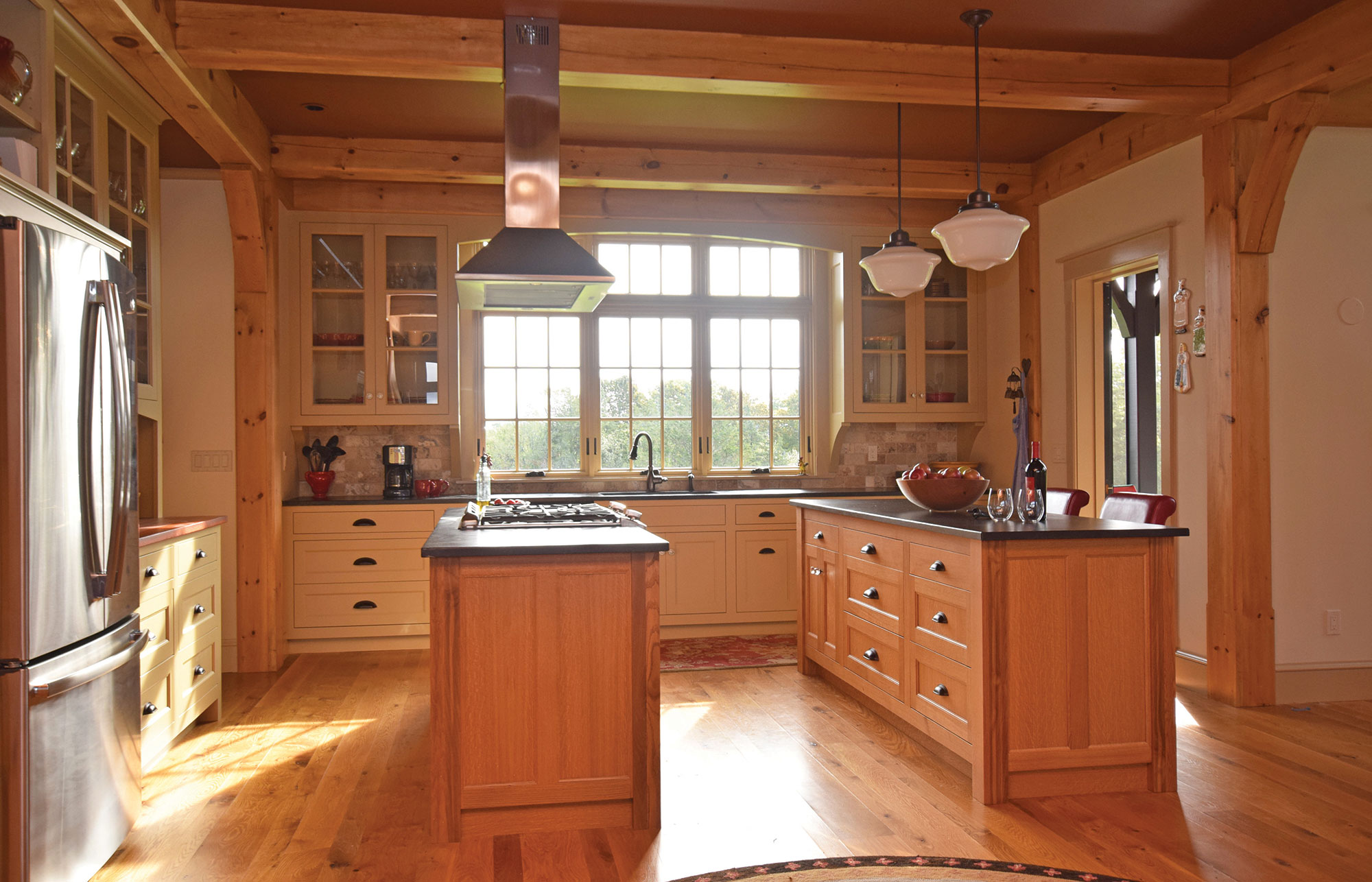 Post & Beam Kitchen - Natural wood islands and a beautiful painted finish on the surrounding cabinets combine to create a truly elegant kitchen in this post & beam home. More pictures