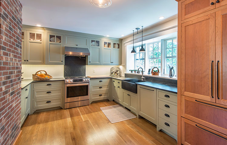 Historic New England Kitchen - Combination of cherry and painted cabinetry enhance this historically accurate kitchen remodel. Custom appliance panels hide dishwasher and fridge behind beautiful wood. More Pictures
