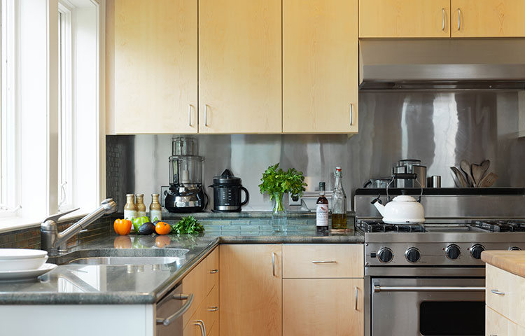 Clean and Sleek Kitchen - Award Winner - Maple slab fronts and a rounded peninsula give this kitchen a modern, clean flair. - More Pictures