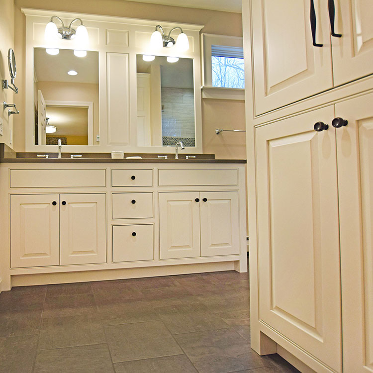 White Bath Cabinetry - Double bowl vanity with raised panel doors and elegant mirror surround. More Pictures