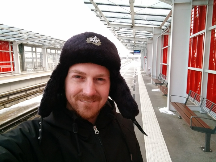 Here I am wearing my ushanka on the train platform at the Gdańsk Airport, with some snow visible here and there behind me.