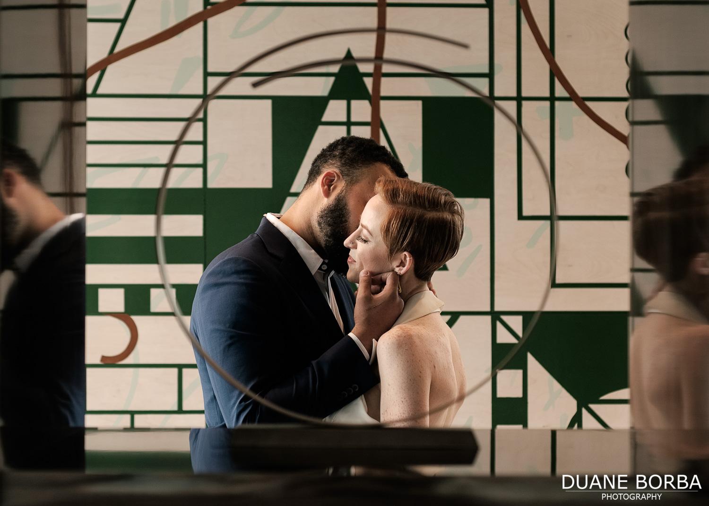 Bride and groom embrace in front of artwork in 505 Nashville