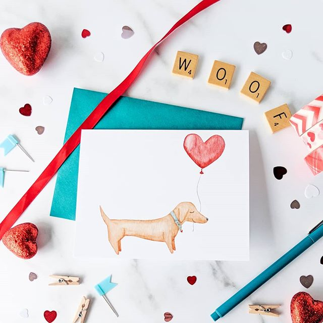 "Puppy love. Valentine's Day is right around the corner. January has suddenly started flying by 😯 Slow down there just a bit Mr. Calendar, I have things to get done and need a bit more time! Cards are available in the shop, poke the photo to grab yours! And while we're on the subject of cards, did you know all my paper products are printed locally? Yep! Wrapping paper, notebooks, sticker seals, even my mugs! It's a coming misconception that all my items are mass  produced by some mthing far away. The truth is, I pick up all my printed goods and get to chat with the family and people who print my items. Nothing comes ""assembled"" so that means all your cards and folded by me, not a machine, and paired with the perfect envelope, stuffed and sealed and shipped out to you. and I still hand address everything so I can use fun mailing lables. Just because it looks professionally mass produced doesn't mean it was! I'm really proud that I get to handle every single item and order and put a little extra love and care into each piece and package. I know this won't always be the case (I really needed an elf and a label printer over Christmas!), but I'm really happy I get to do it in the meantime. Do you have any questions about what I do or how do it? Ask below and I do my best to answer! . . . . . #valentine #valentinesday2019 #valentinescard #dachshundvalentine #dachshund #dachshund_love #dachshundsofinstagram #valentines #sharethelove #lovecard #stationery #greetingcard #dogcard #dachshundcard #hearts #heartballoon #woof #iloveyou #greetingcards #greetings #etsylove #etsyshop #etsyvalentines #gimmeallyourlove #sweetheart #doglovers #handmade #etsyhandmade @etsy"