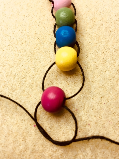 7. Final Tying. Take the two strings and tie a final double knot so the bead won't come off. Be sure to keep the space above the final bead while you make the final knot. You can also add a tassel here if you would like. I didn't do that.